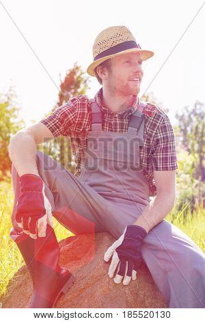 Thoughtful gardener looking away while sitting on rock