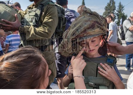 Unidentified Kid Get Camouflage Make-up  Face Paint By Israeli Girl Soldier At Latrun Armored Corps