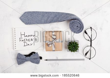 Happy Fathers Day background with notebook gift glasses necktie and bowtie on light working desk top view in flat lay style.