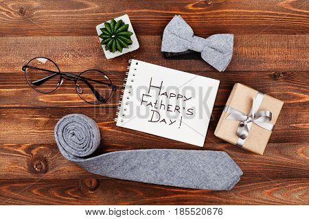 Happy Fathers Day background with notebook gift glasses necktie and bowtie on wooden rustic table top view in flat lay style.