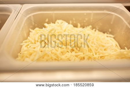 cooking, storage and food concept - container with grated cheese at restaurant kitchen