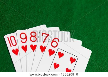 casino, gambling, games of chance, hazard and entertainment concept - straight flush poker hand of playing cards on green cloth