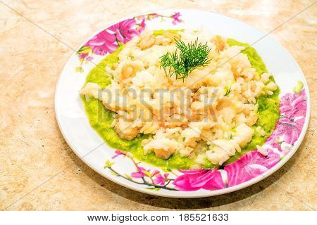 Plate with prawns and shrimps risotto on spinach bed