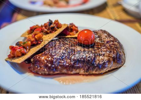 Grilled beef steak with tomato and bruschetta with vegetables