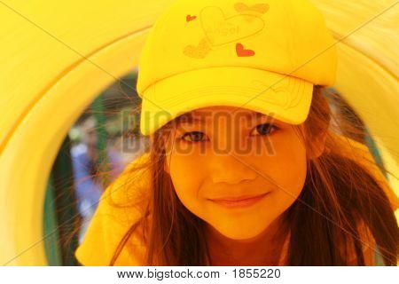 Spunky Little Girl Playing Inside Yellow Tube