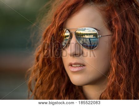 Portrait of red-haired girl in the nature