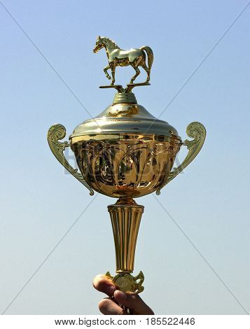 PYATIGORSK; RUSSIA - MAY 02; 2013:Classic Gold Cup with the image a horse a pedestal with the engraved inscription