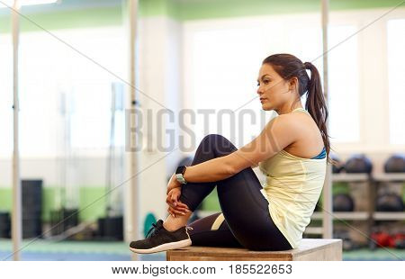 sport, fitness, lifestyle and people concept - woman with heart rate tracker or smartwatch in gym