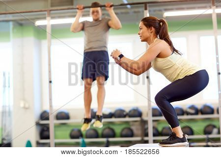 fitness, sport, training, exercising and people concept - woman and man doing pull-ups and box jumps in gym