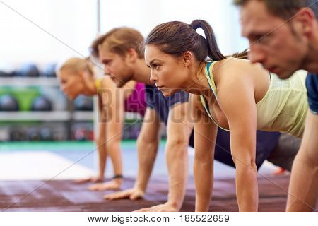 fitness, sport, exercising and people concept - woman doing straight arm plank at group training in gym