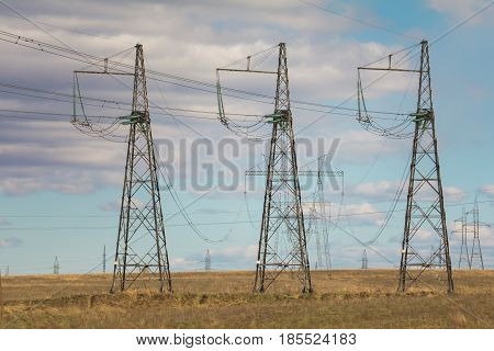 Electricity pylons and lines at summer field, sunny day, telephoto