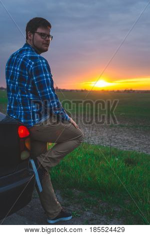 car trip man stops to look sunrice on the highway, car travel
