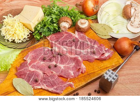 Sliced uncooked pork neck on the wooden cutting board and other ingredients for cooking pork chops baked with onion mushrooms and cheese closeup beside meat tenderizer on a wooden surface