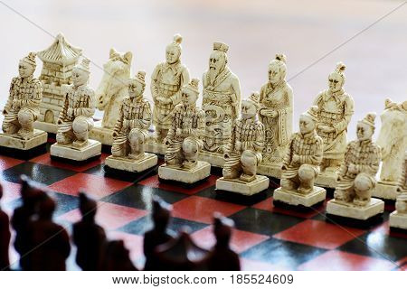 Carved Chess Pieces In Chinese Style On A Chessboard.