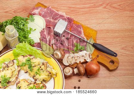 Fragment of the dish with pork chops baked with onion mushrooms and cheese and beside raw meat and meat tenderizer on it other ingredients for preparation of chops closeup on a wooden surface