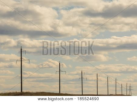Row of electricity pylons and lines at summer field, sunny day, telephoto