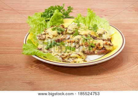 Several pork chops baked with onion mushrooms and cheese and decorated with twigs of the parsley and lettuce leaves on the yellow and white dish on a wooden surface