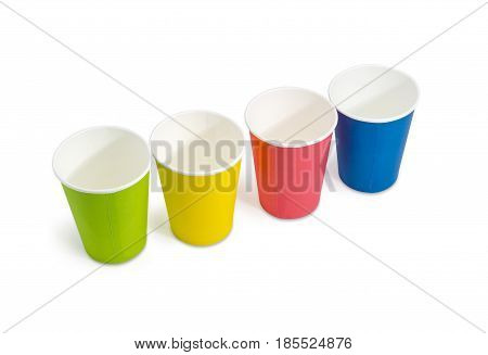 Row of the disposable paper cups in red green blue and yellow colors on a light background