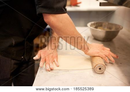 cooking, baking and people concept - close up of male chef with rolling-pin rolling dough at restaurant or bakery kitchen