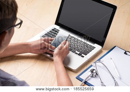 Male doctor using a laptop and smartphone sitting at his desk