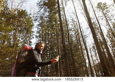Disoriented hiker checking her phone for GPS coordinates being lost in the woods looking for the right direction. Adventure active lifestyle mobile phone dependency being lost concept.