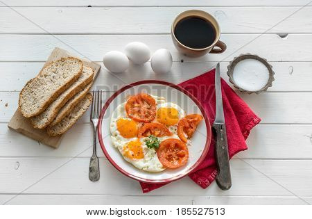Eggs fried overeasy served on white plate, tableware and red napkin, coffee on side