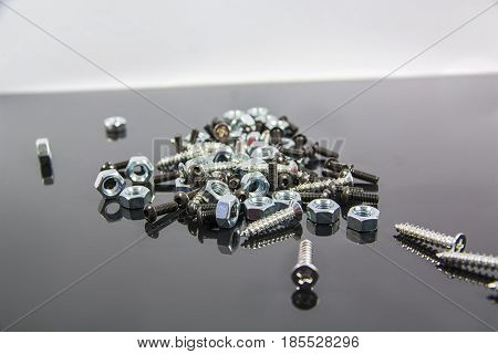 Close-up of heap of bolts, screws and nuts on neutral background in studio shot