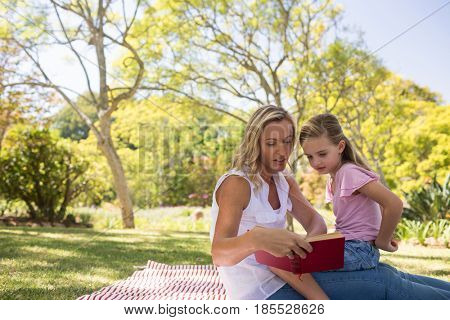 Mother and daughter reading novel in park on a sunny day