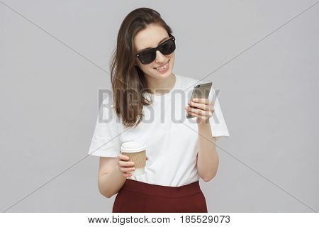 Shot Of Cheerful Girl Isolated On Gray Background With Sunglasses And Casual Clothes Holding Cup Of
