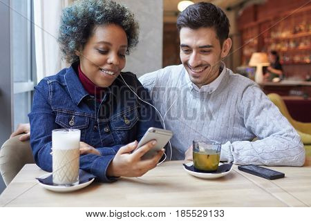 Shot Of Interracial Lovers Sitting In A Cafe Enjoying Their Date, Drinking Coffee And Tea And Sharin
