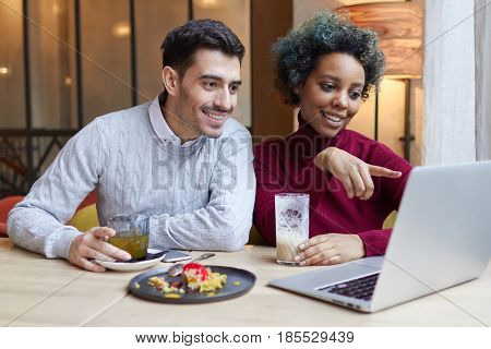Portrait Of Happy Lovers Meeting Indoors With Laptop Open On Table In Cafe. Dark-skinned Girl Is Poi