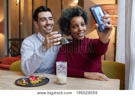 Happy Interracial Couple Dating In Cafe In Afternoon, Dark-skinned Woman Is Stretching Her Hand Hold