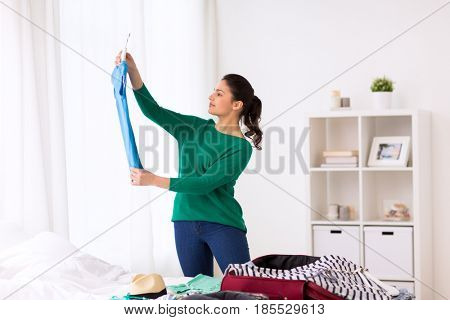 tourism, people and luggage concept - happy young woman packing travel bag at home