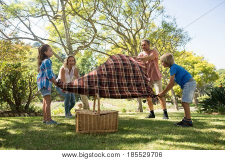 Family spreading the picnic blanket in park