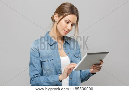 Closeup Portrait Of Happy Young Woman Using Tablet Pc Isolated On Grey Background. Side View Of A Sm