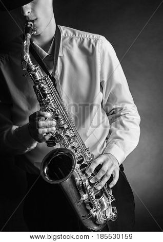 Young male performer playing saxophone. Black and white image