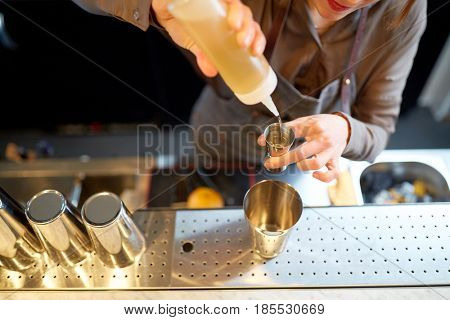 alcohol drinks, people and luxury concept - woman bartender with shaker pouring syrup into jigger and preparing cocktail at bar counter