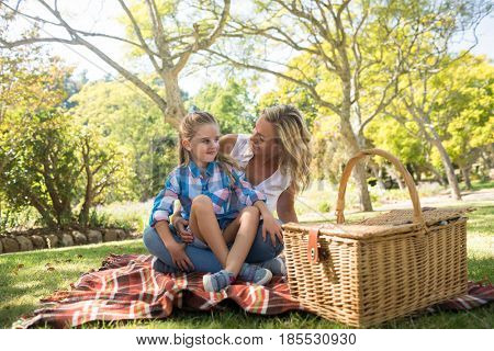Daughter sitting on mothers lap while having picnic