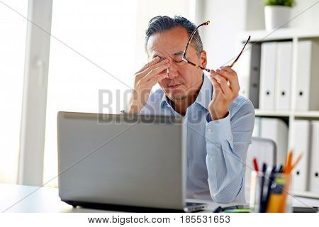business, overwork, deadline and people concept - tired businessman with eyeglasses and laptop computer rubbing eyes at office