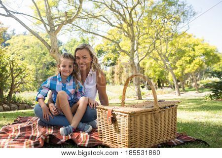 Daughter sitting on mothers lap while having picnic in the park