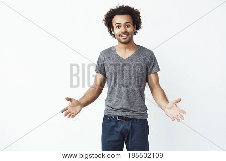 Stylish and handsome african man with arms wide open against white wall inviting to a gig. Copy space.