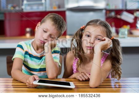 Bored siblings with digital tablet in kitchen at home