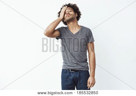 Upset and sad african man grabbing his forehead with hand standing missing the diversity lottery application deadline or forgetting to turn of electricity at home over white background. Copy space.