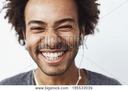 Close up portrait of young happy african man smiling listening to upbeat streaming music laughing over white background. Youth concept. Copy space.