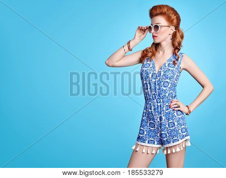 Fashion Redhead Model in Sexy Jumpsuit, woman in Trendy Summer Dress. Stylish wavy hairstyle, fashion Sunglasses, Summer Floral Outfit. Glamour fashion pose.Playful Beauty Girl, Luxury summer Lady