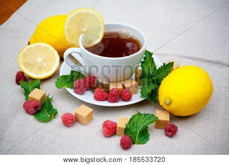 Tea with mint brown sugar raspberry and lemon on table