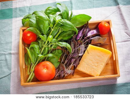 Green and purple basil chunk of parmesan cheese and tomatoes on wooden tray
