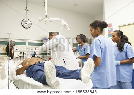 Doctor and nurses working on patient in emergency room