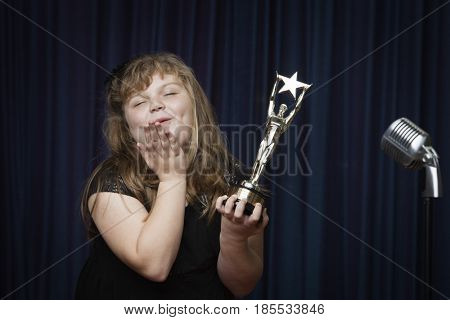 Caucasian girl holding trophy and blowing kisses in stage