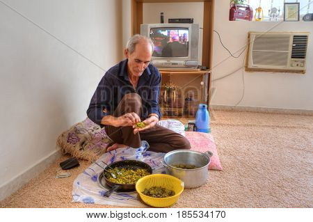 Bandar Abbas Hormozgan Province Iran - 15 april 2017: One elderly muslim man is cooking a national persian dish dolmeh sitting on the carpet in his house.